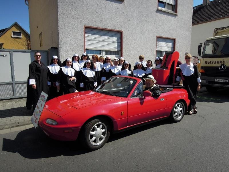 """Im Bild die Damen von den """"Sistern in Red Shoes"""" und dem Gemischten Chor. Im Vordergrund Norbert Roschke in seinem Cabriolet mit einem überdimensionalen """"Red Pumps"""" auf dem Kofferraumdeckel."""